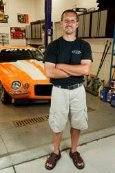 View of Randy Johnson in front of the Orange Peeler Camaro t his shop D&Z Customs